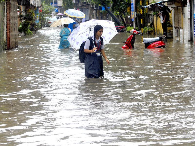 A school girl walks through a waterlogged road at Dadar after heavy rains in Mumbai.