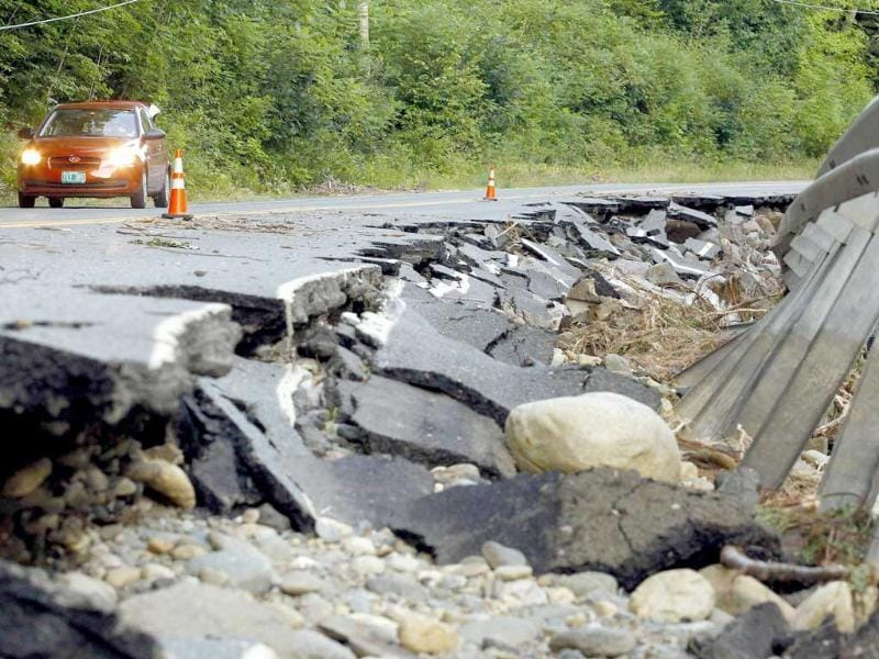 A car passes a section of Route 112 that was washed out during Hurricane Irene in Halifax, Vermont.
