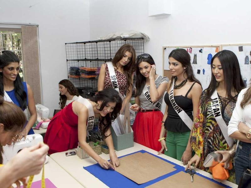 Miss El Salvador 2011 Mayra Aldana (2nd L) draws on fabric as Miss India 2011 Vasuki Sunkavalli (L), Miss Spain 2011 Paula Guillo (5th R), Miss Great Britain 2011 Chloe-Beth Morgan (4th R), Miss Lebanon 2011 Yara El Khoury-Mikhael (3rd R), Miss Japan 2011 Maria Kamiyama (2nd R) and Miss Portugal 2011 Laura Goncalves look on during a visit to the Escola de Moda fashion school in Sao Paulo.