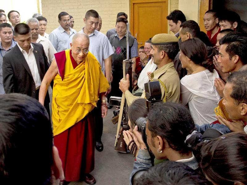 Tibetan spiritual leader the Dalai Lama is greeted by devotees as he arrives at the Tsuglakhang temple to deliver a religious talk in Dharamsala.