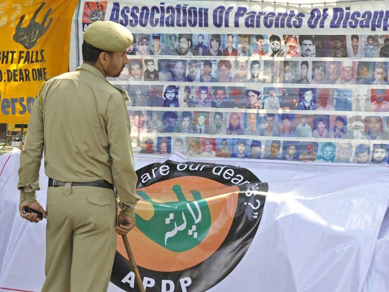 A policeman looks at portraits of missing people during a protest rally to demand information of their whereabouts during the International Day of the Disappeared in Srinagar.