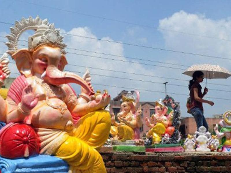 A lady walks by a roadside stall with Ganesh idols on the eve of Ganesh Chaturthi starting September 1.