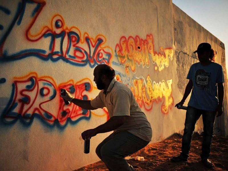 Libyans paint anti-Gaddafi graffiti on a wall in central Tripoli.