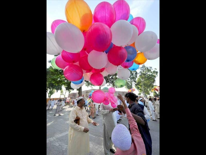 Pakistani Muslims buy balloons for their children after offering Eid al-Fitr prayers outside the Red Mosque during the first day of their religious festival in Islamabad.