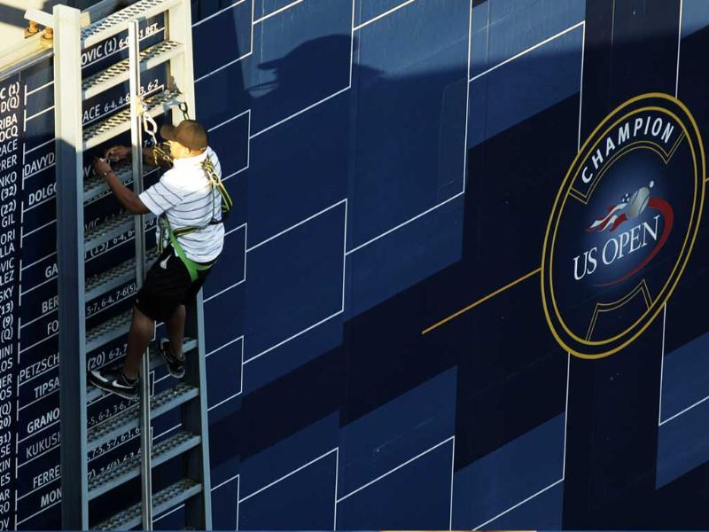 A man changes the bracket displayed during the first round of the US Open tennis tournament in New York.