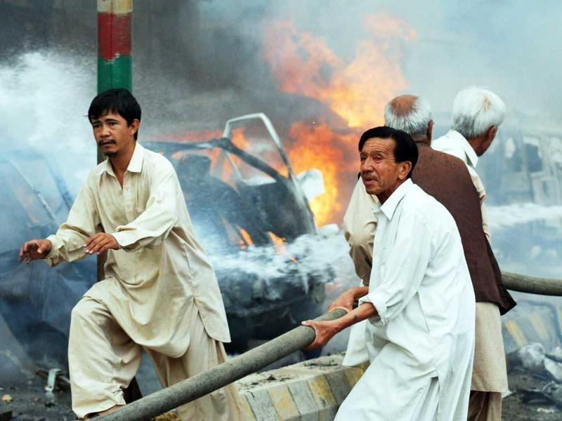 Local residents attempt to extinguish burning vecicles after a car bomb blast in Quetta. A car bomb exploded in a parking lot after Eid prayers, killing at least four people and wounding 10 others in the restive southwestern Pakistani city of Quetta, police said.
