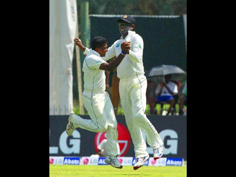 Sri Lanka's Rangana Herath (L) celebrates with Angelo Mathews taking wicket of the Australia's Ricky Ponting during the first day of their first Test match in Galle.