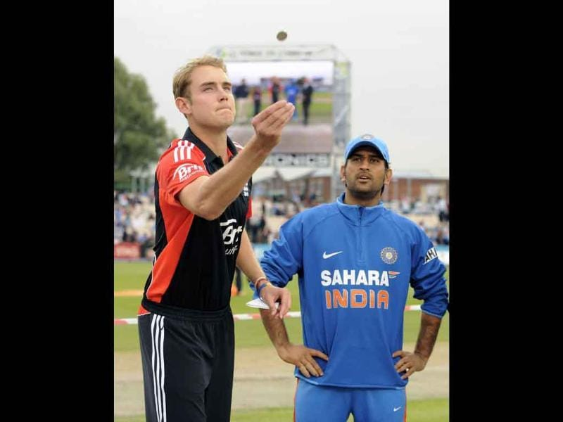 England's captain Stuart Broad (L) tosses the coin watched by India's Mahendra Singh Dhoni before the Twenty20 international cricket match at Old Trafford cricket ground in Manchester.