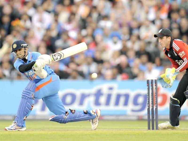 Rahul Dravid hits out watched by England's Craig Kieswetter (R) during the Twenty20 international cricket match at Old Trafford cricket ground in Manchester.