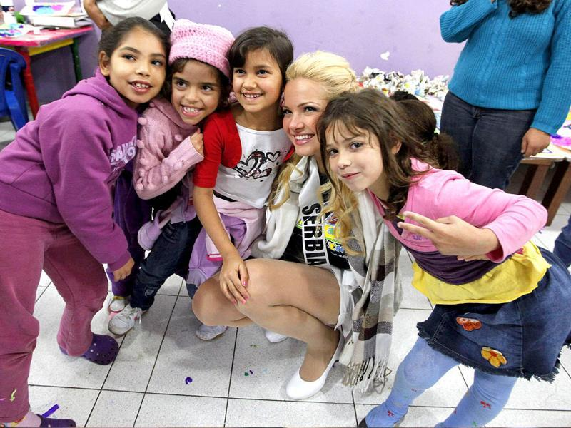 Miss Serbia 2011 Anja Saranovic poses with chidren for a photograph at the Casa do Zezinho, a non-governmental organization in Sao Paulo. The contestants are in Sao Paulo for the 2011 Miss Universe pageant which will be held September 12.