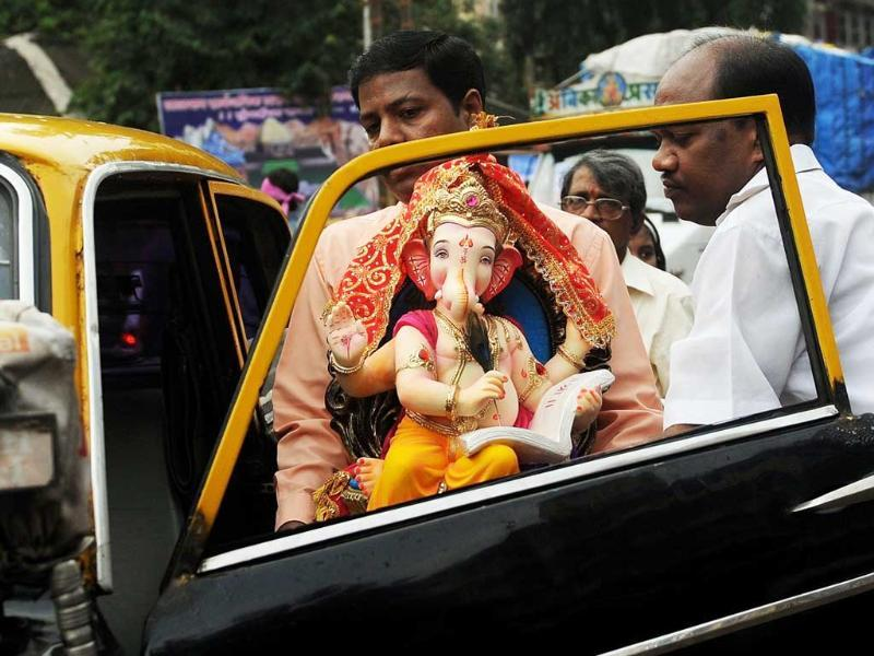 Devotees get into a taxi with an idol of Lord Ganesh in Mumbai. Hindu devotees bring home idols of Lord Ganesha in order to invoke his blessings for wisdom and prosperity, ahead of the eleven-day long Ganesha Festival and culminates with the immersion of the idols in the Arabian Sea.