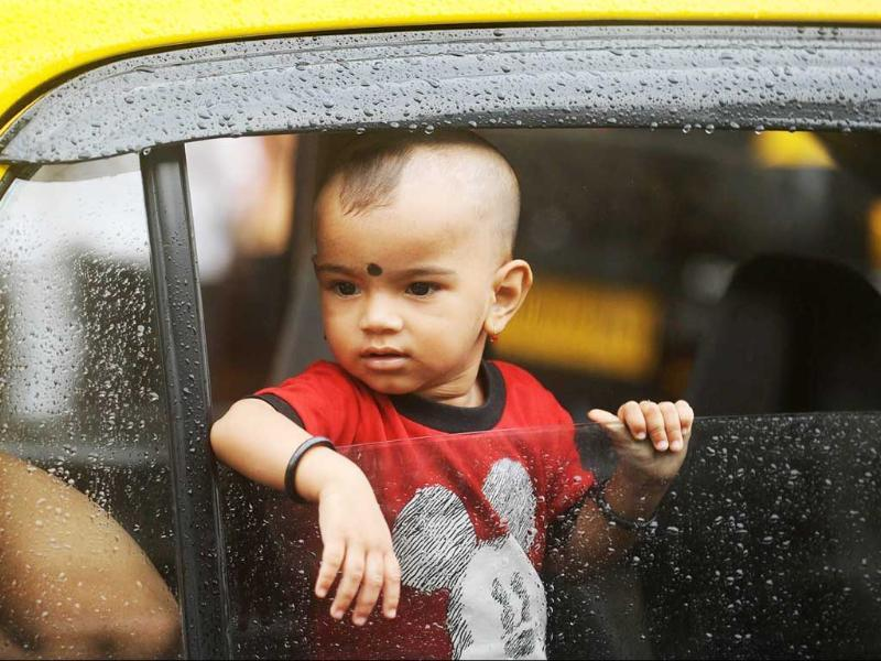 A child looks out from a taxi window during Ganesh festival processions in Mumbai.