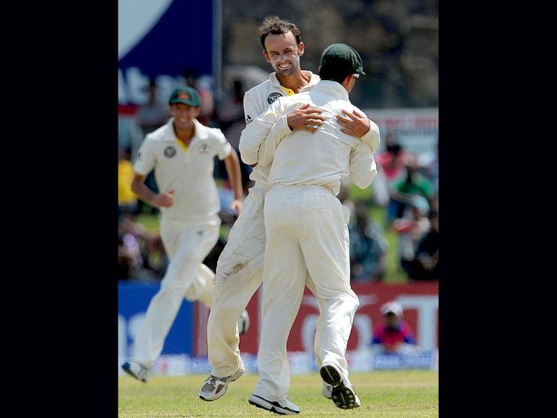 Australia bowler Nathan Lyon (C) celebrates with his teammate Ricky Ponting (R) after he dismissed unseen Sri Lankan batsman Angelo Mathews during the second day of the Test match.