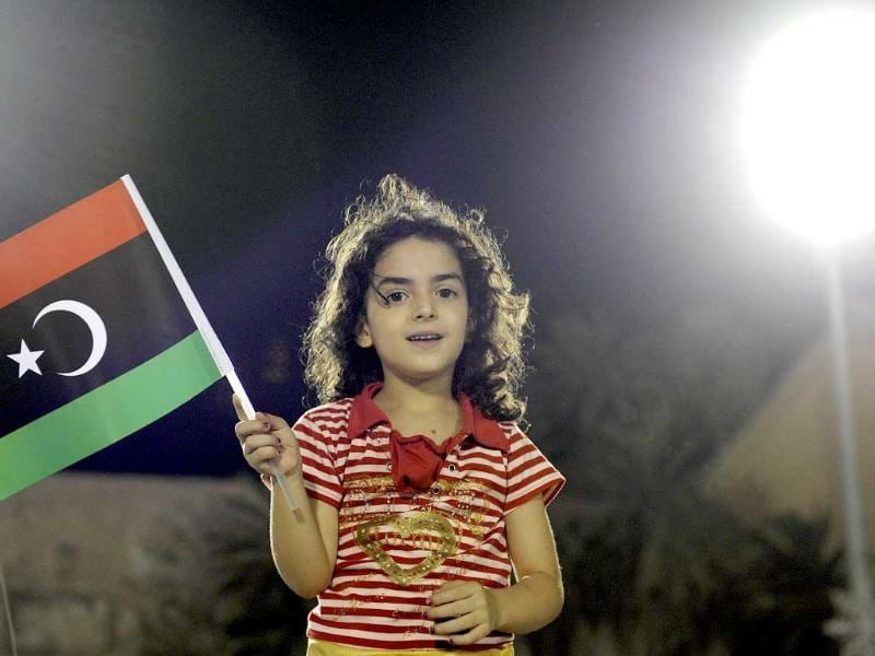 Libyans celebrate with their new flag at Martyrs Square in Tripoli.
