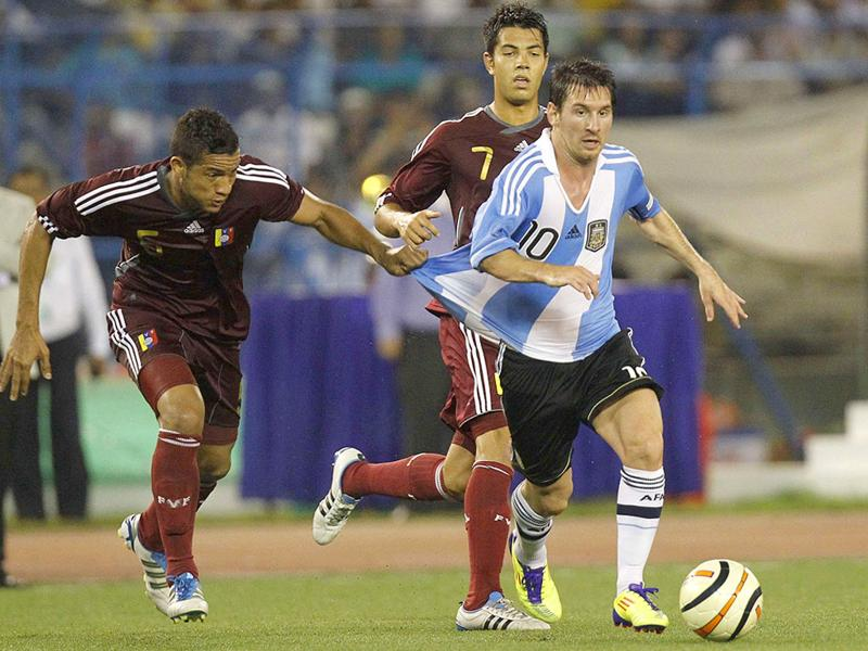 Venezuela's Agnel Flores (L) and Nicolas Fedor fight for the ball with Argentina's Lionel Messi (R) during their international friendly soccer match in Kolkata.