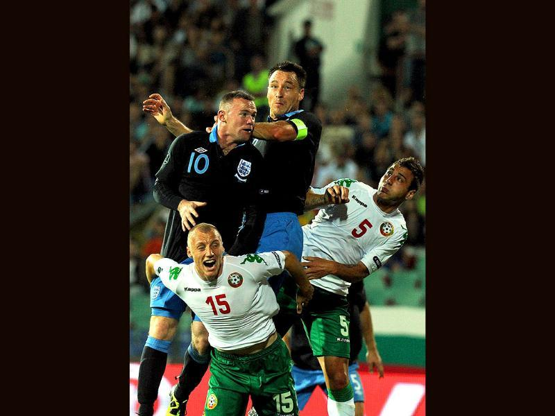 England forward Wayne Rooney (top L) scores a goal against Bulgarian during the Euro 2012 qualifying football match at the Vassil Levski stadium in Sofia.