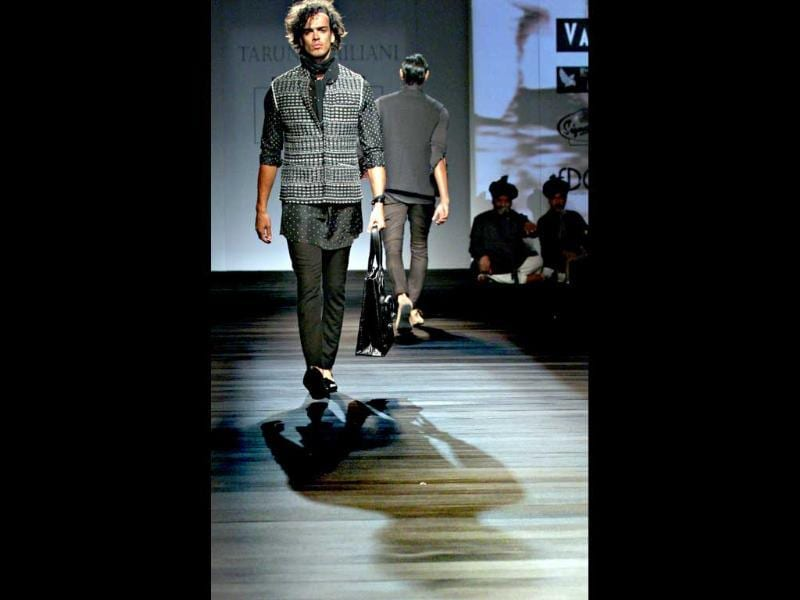 With a leather bag and fitted jacket, a model makes a style statement on the ramp. (Pic: Jasjeet Plaha)
