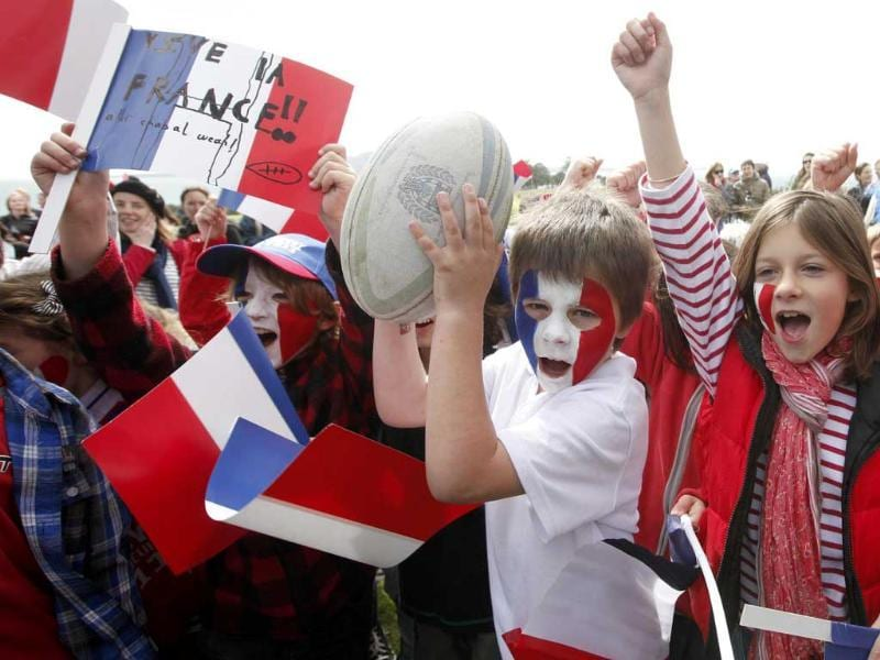 Children cheer France's rugby team players during an official welcome ceremony for the 2011 Rugby World Cup in Auckland.