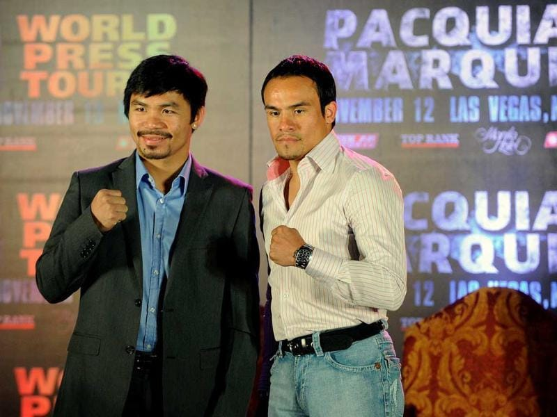 Eight-time world boxing champion Manny Pacquiao (L) of the Philippines and Mexican Juan Manuel Marquez (R) pose for the media in Manila, for the start of a series of a four-city international media tour.