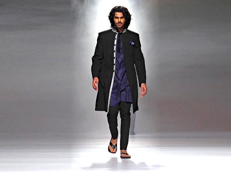 A model looks dapper in a collared kurta and with churidaar by Rajvi Mohan.