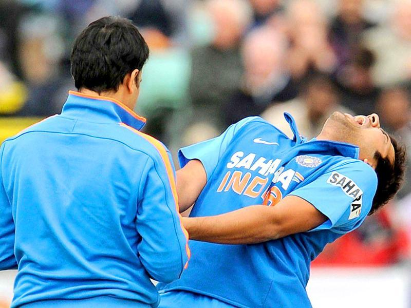 Rohit Sharma (R) reacts after he was hit on the finger with the first ball that he faced as it is inspected by the physiotherapist during the first one-day international cricket match against England at the Riverside cricket ground in Chester le Street, England.