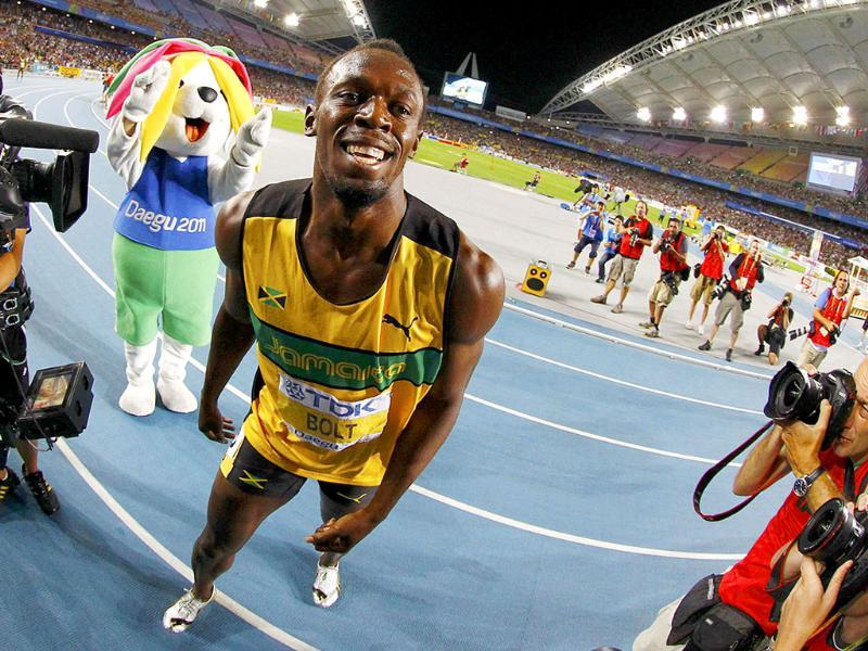 Official mascot Sarbi is seen (L) as Usain Bolt of Jamaica celebrates winning the men's 200 metres final at the IAAF World Athletics Championships in Daegu.