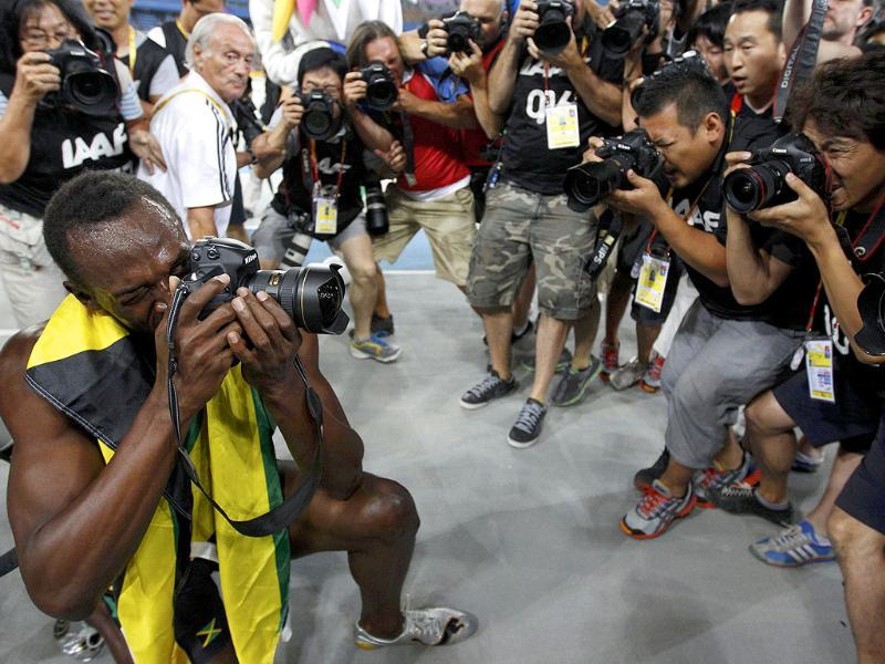 Usain Bolt of Jamaica uses a camera after winning the men's 200 metres final at the IAAF World Athletics Championships in Daegu.