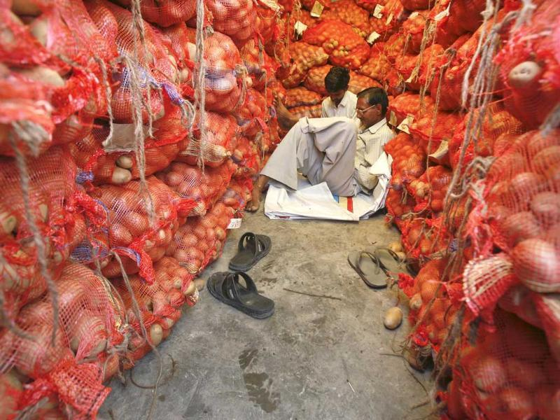 Men sit amid stacked sacks of potatoes at a vegetable wholesale market in Noida, on the outskirts of New Delhi.