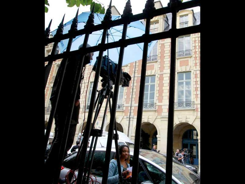 Members of the media wait outside the residence of former IMF chief Dominique Strauss-Kahn after his return to Paris.
