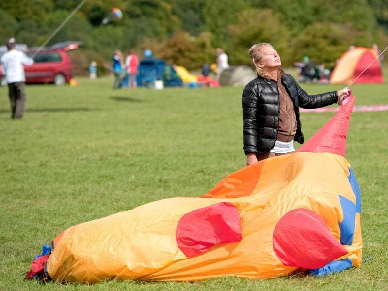A woman enjoys the sun's heat as she holds the line of a kite at the 25th annual Bristol International Kite Festival on the Ashton Court Estate near Bristol.