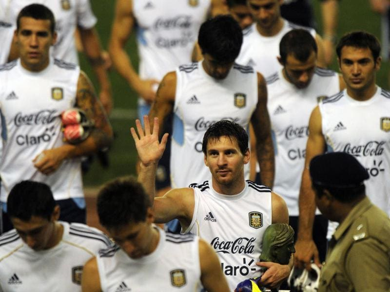 Argentine footballer Lionel Messi (C) gestures to supporters following a training session in Kolkata.