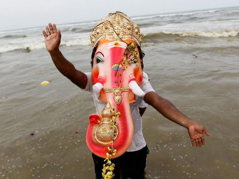 A devotee carries an idol of Lord Ganesha for immersion in Marina beach during Ganesh Utsav in Chennai.