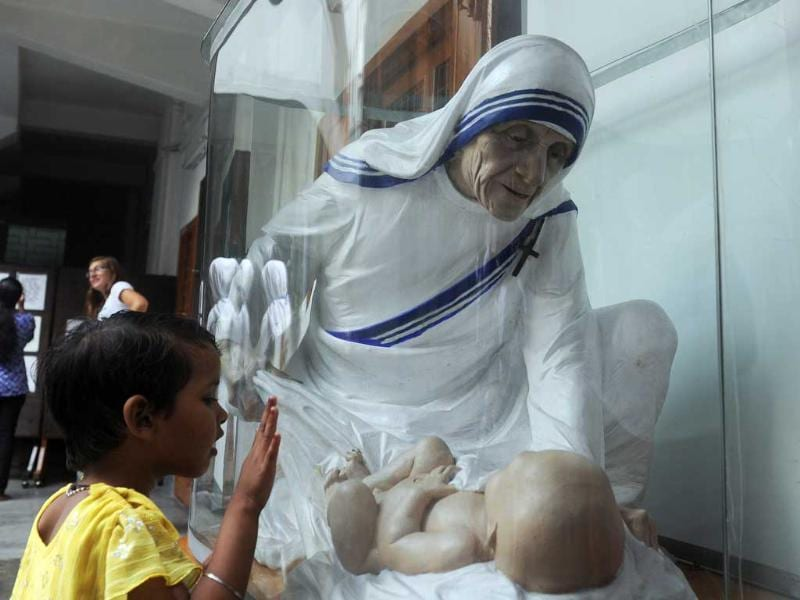 A Christian touches the glass near a statue to pay tribute to Mother Teresa, in front of her tomb, at Mother House in Kolkata.