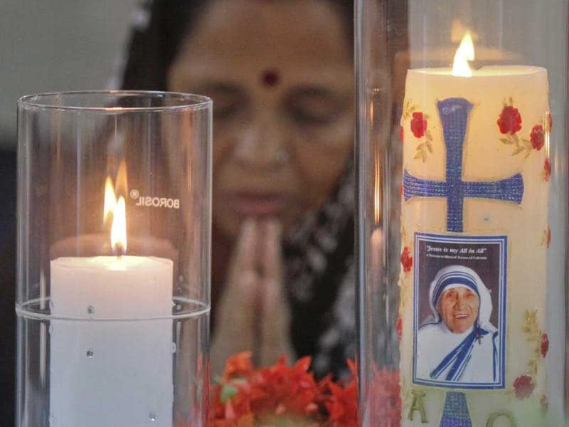 A candle, adorned by an image of Mother Teresa, burns as a woman pays her respects during a ceremony marking Mother Teresa's death anniversary in Kolkata.