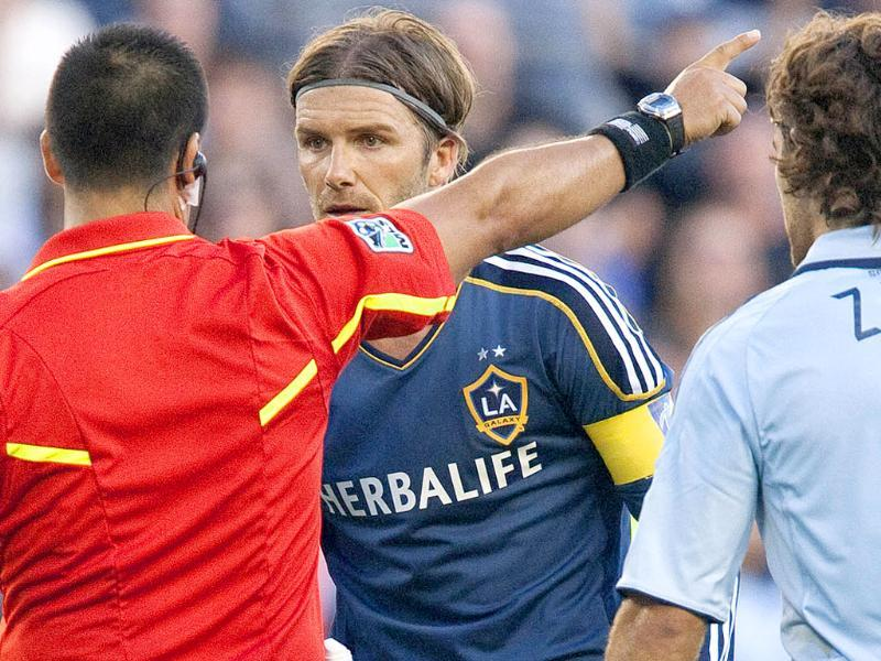 Los Angeles Galaxy's David Beckham, center, is issued a yellow card for time wasting during a MLS soccer game against Sporting Kansas City at Livestrong Sporting Park in Kansas City, Kan.