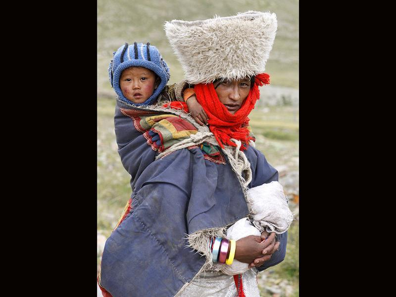 A Tibetan woman is seen on a mountain trekking pilgrimage around Mount Kailash with her child on her back in Ngari, Tibet Autonomous Region.