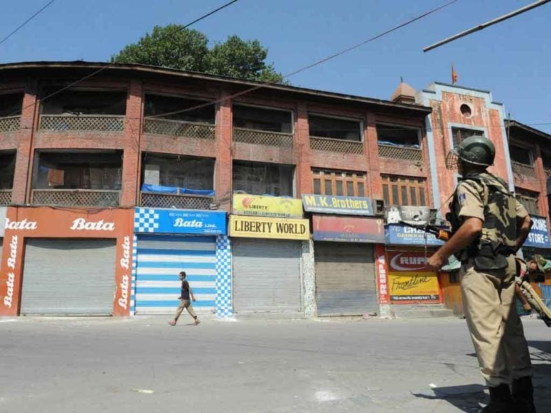 Paramilitary soldiers stand guard near shuttered shops during a strike in Srinagar.