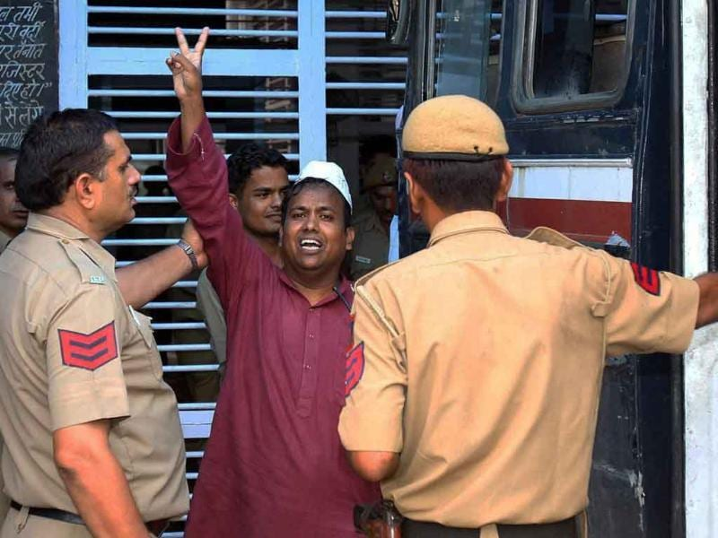Suhail Hindustani, an accused in cash-for-votes scam, flashes the victory sign as he is taken to the Tihar jail after he was produced in Tis Hazari court in New Delhi.