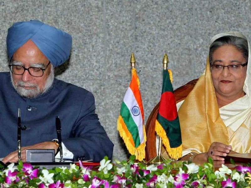 Prime Minister Manmohan Singh signs an agreement as his Bangladeshi counterpart Sheikh Hasina looks on in Dhaka.