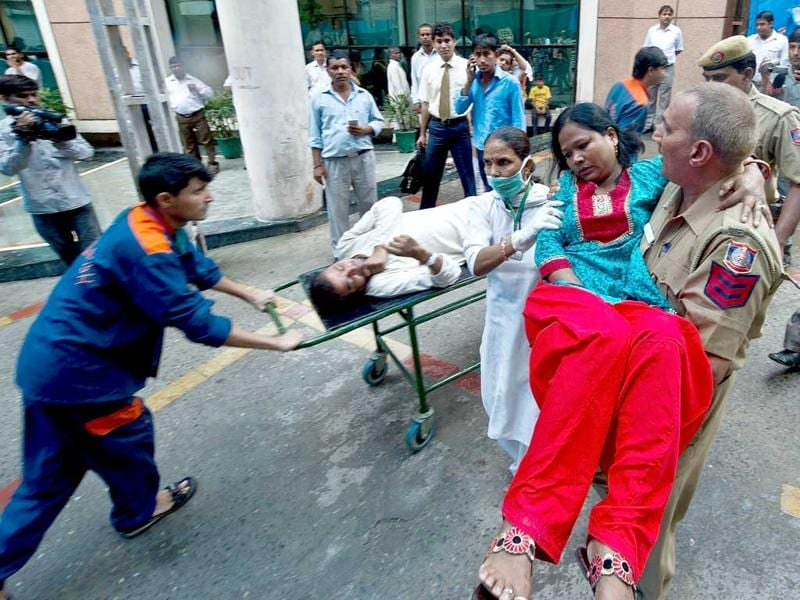 A policeman carries a wounded blast victim at the RML Hospital in New Delhi following a bomb blast at the Delhi high court.