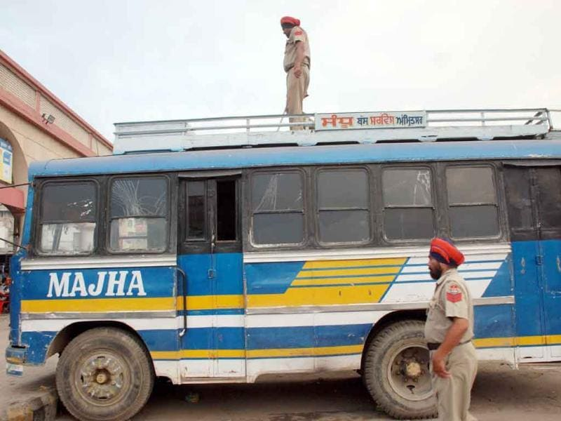 Police personnel checking buses at the Amritsar bus stand follwoing the Delhi high court blast.