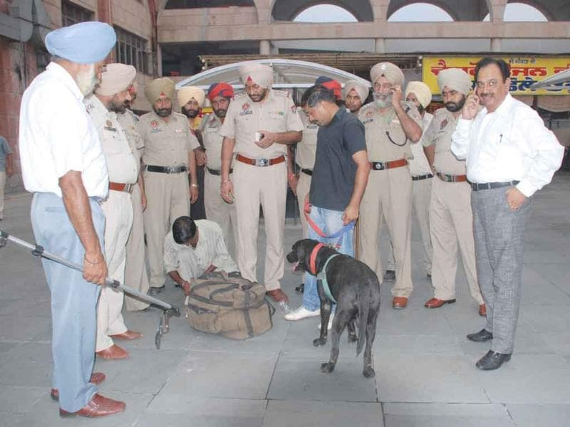 Police checking bags of passengers at the Amritsar bus stand following the Delhi high court blast.