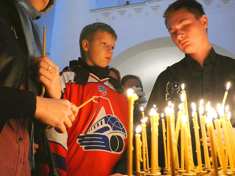 People wearing the club jerseys of Russian ice hockey team Lokomotiv Yaroslavl light candles during a commemorative service in a church in Yaroslavl. At least 44 people were killed when a Russian jet carrying hockey players of Lokomotiv Yaroslavl to their first match of the KHL (Kontinental Hockey League) season crashed on takeoff.