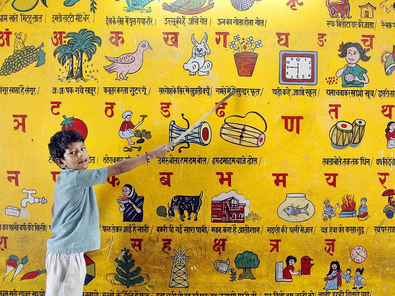 In this photo taken on Wednesday, a young Indian boy reads a picture on a wall at a government run school on International Literacy Day in Allahabad, India.