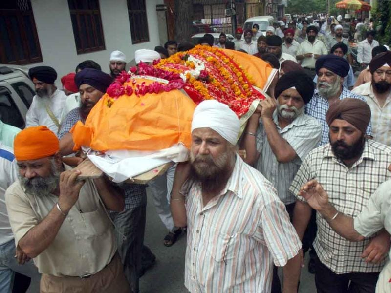 Bhupender Singh, eldest son (white turban center), carrying the dead body of his father Sardar Inder Singh at the Gita Colony Gurudwara in New Delhi.