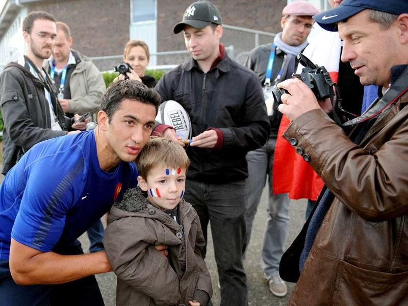 France's rugby union center Maxime Mermoz (L) poses with a young supporter for a picture after a team training session at the Takapuna Rugby Club in Auckland.