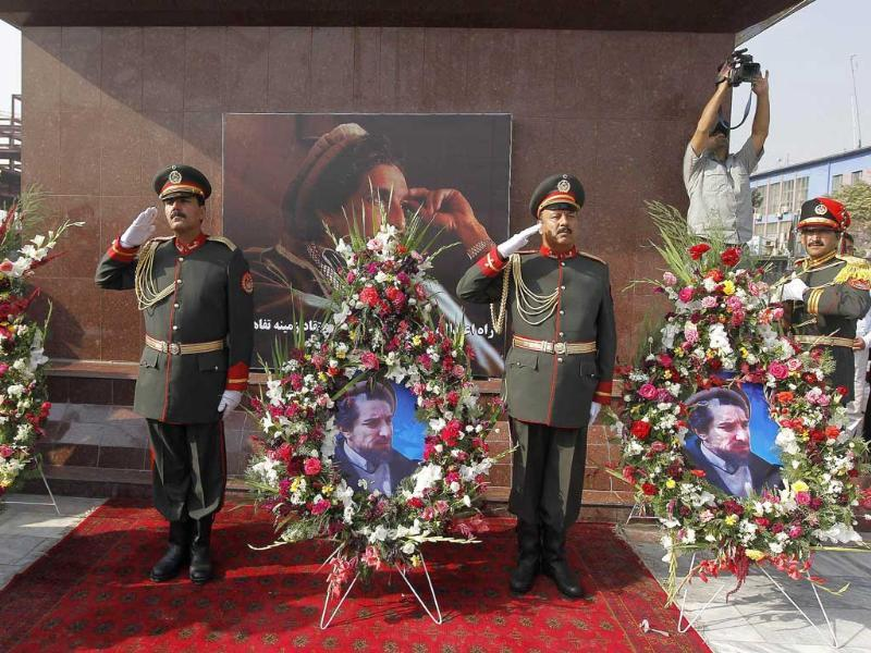 An honour guard of Afghan security personnel salute as they stand beside a floral tribute during a ceremony marking the tenth anniversary of the death of slain Afghan national hero Ahmad Shah Masood in Kabul.