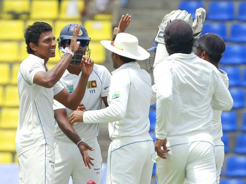 Sri Lanka's Suraj Randiv (L) celebrates with teammates taking the wicket of Australia's Phillip Hughes during the second day of their second Test cricket match against Australia in Kandy.