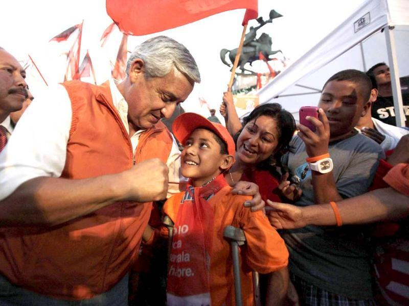 Guatemala's presidential candidate Otto Perez Molina (L) from the Patriot Party (PP) interacts with a young supporter before his final political rally ahead of elections in Guatemala City.