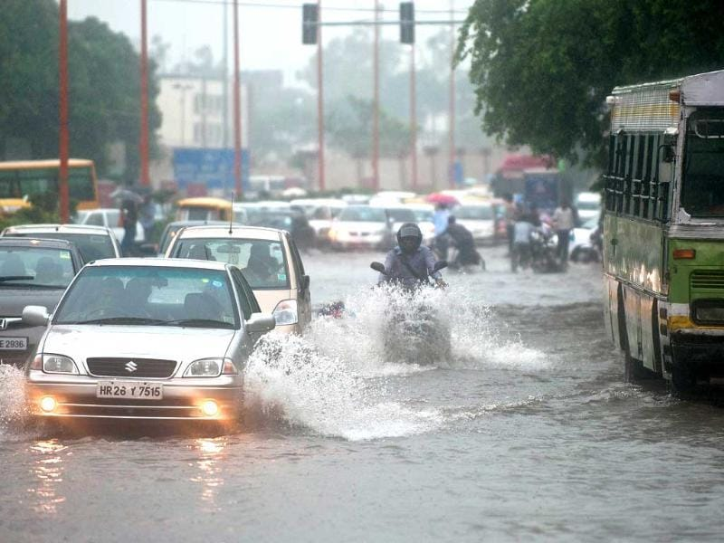 Office-goers travel through a water-clogged road following heavy rainfall in New Delhi.